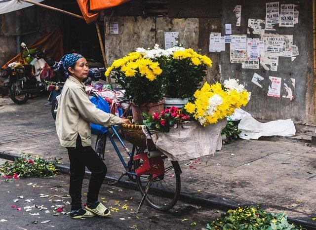 Blumenverkäuferin auf dem Markt in der Altstadt von Hanoi