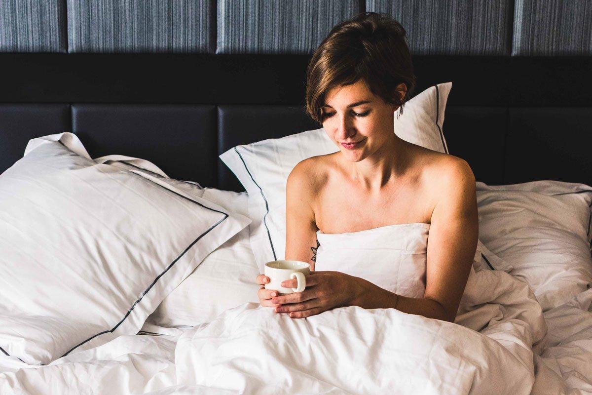 Mit Tasse Kaffee im Hotelbett
