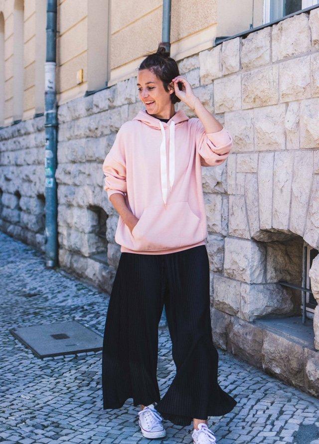 Outfit mit rosa Kapuzenpullover und schwarzen Culottes