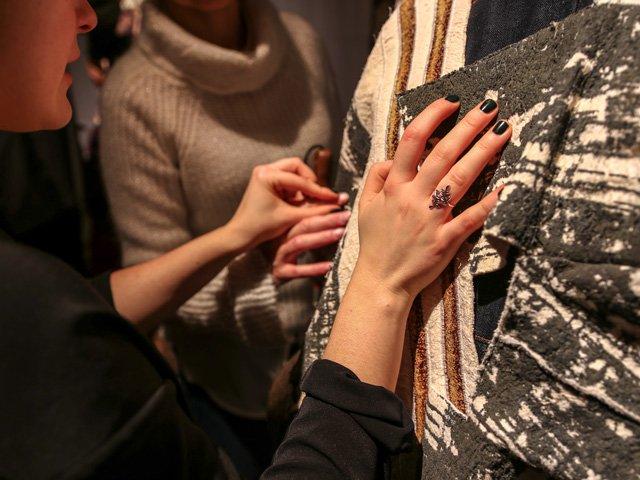 Designerin und Besucherin befühlen die Kleidung