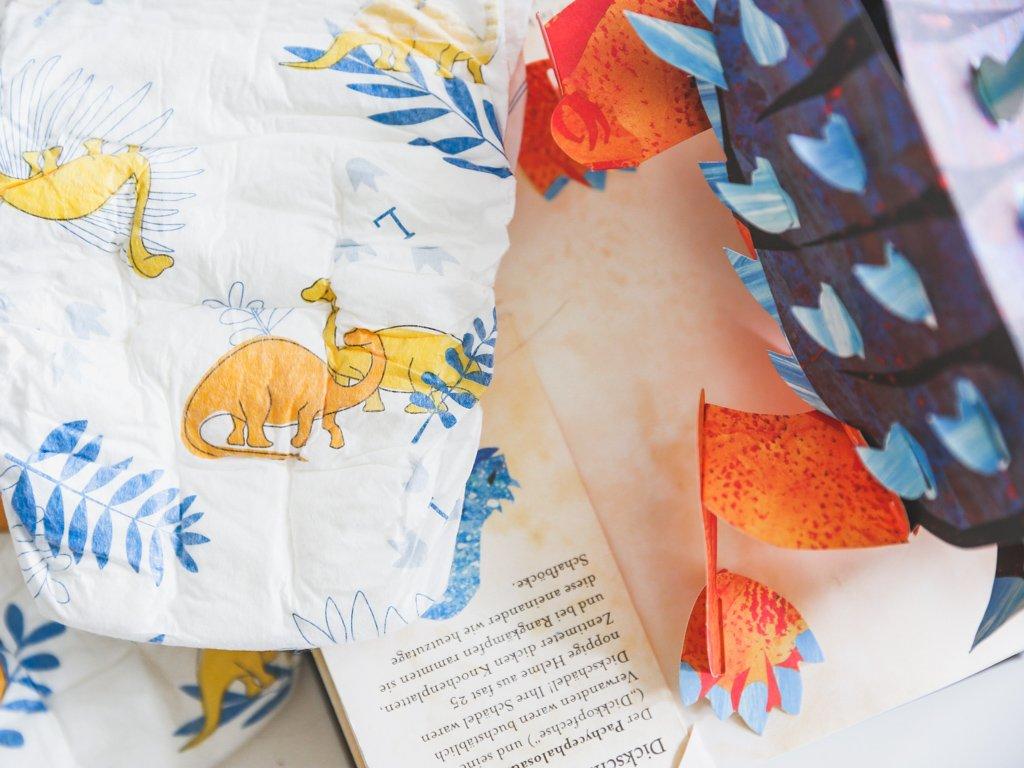 Windel von Lillydoo neben Pop up Buch mit Dinosauriern